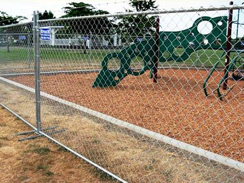 Galvanized chainlink temporary fencing for playground and a green slid in it.