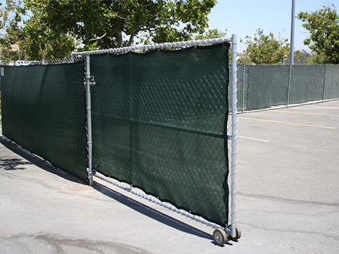 Galvanized chain link fencing with shade cloth for windbreak.